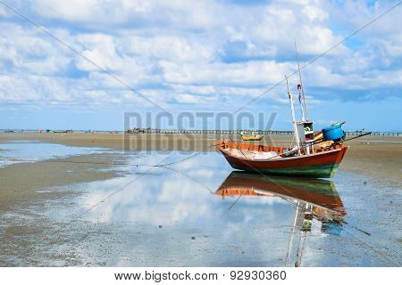 Reflection Of Fishing Boat On Beach With Jetty Background
