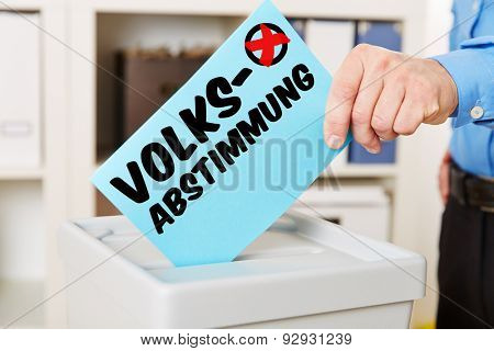 Hand with ballot paper on box with German word Volksabstimmung (referendum)