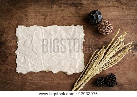 Old Wrinkled Paper On Old Wood Background With Dried Flower