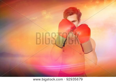 Muscly man wearing red boxing gloves in guard position against desert landscape