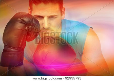 Close-up of a determined male boxer focused on training against purple and orange sky