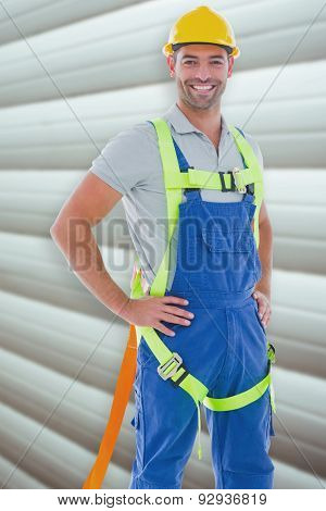Builder in safety gear against grey shutters