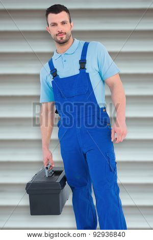 Repairman with toolbox against grey shutters