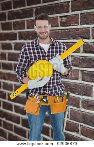 Handyman holding hard hat and spirit level against red brick wall