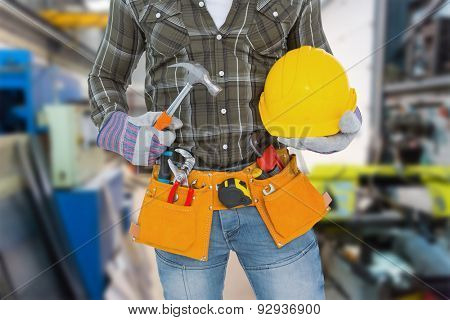 Manual worker wearing tool belt while holding hammer and helmet against workshop