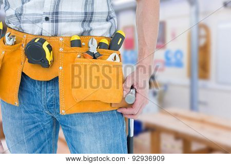 Technician with tool belt around waist against workshop