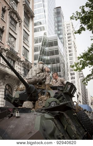 NEW YORK - MAY 21 2015: Two US Marines sit on top of a military tank parked on the street during a demonstration for the public at Bryant Park for Marine Day during Fleet Week NY.