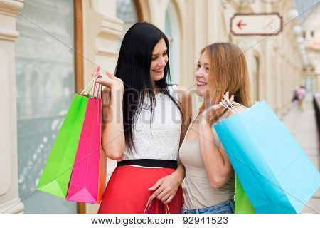 Two Chatting Young Women Are Walking Through The Fancy Shop With The Colourful Shopping Bags.