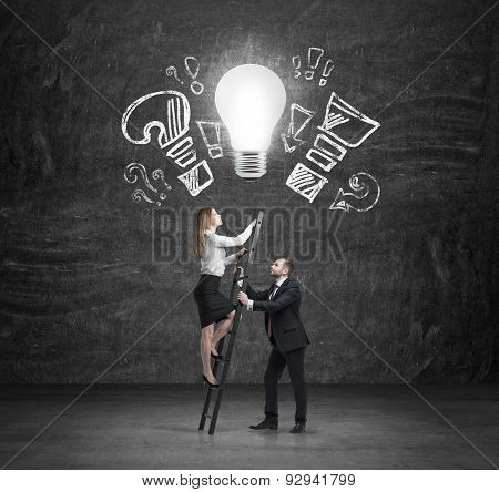Businessman Holds A Ladder For Business Lady Who Is Climbing Up. The Concept Of The Teamwork And Coo