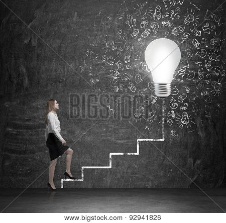 Young Lady Is Going Up Via The Drawn Ladder To The Huge Lightbulb. A Concept Of Ideas In Business.