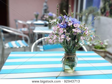 table with fresh wild flowers in cafe, image toned and noise added