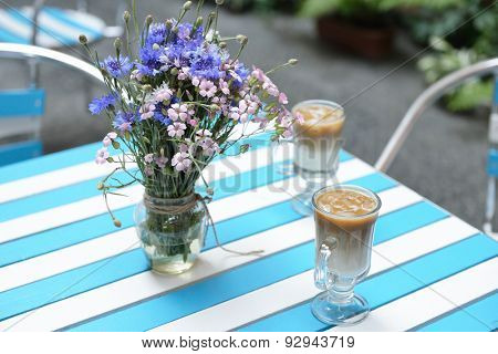 table with fresh wild flowers and ice coffee in cafe, image toned and noise added