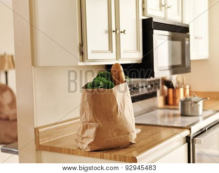 paper grocery bag of freshly bought food from store sitting on kitchen counter