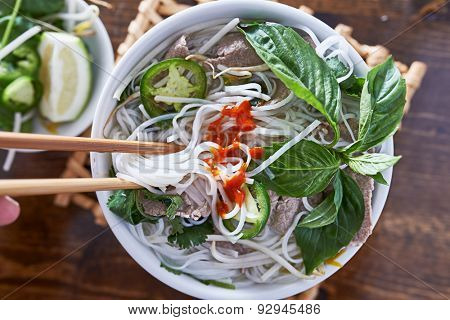 eating beef pho with spicy sriracha sauce shot top down