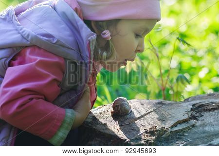 Three Years Old Preschooler Girl Blowing On Crawling Edible Snail