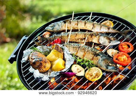 Grilled mackerel fish with baked potatoes over the coals on a barbecue