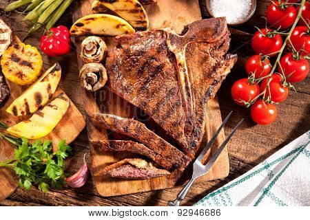 Beef T-bone steak with grilled vegetables and seasoning on wooden background