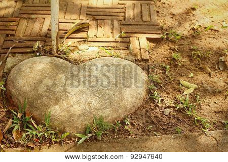 Brown Stone Of Heart In A Garden.