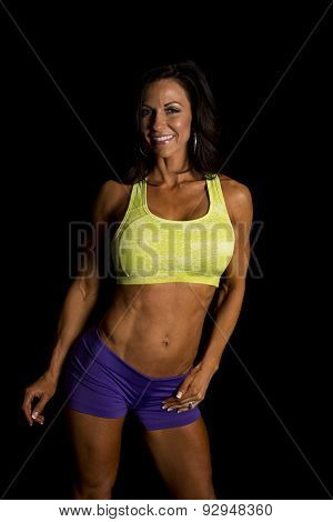 Woman Blue Shorts And Green Sports Bra Stand On Black