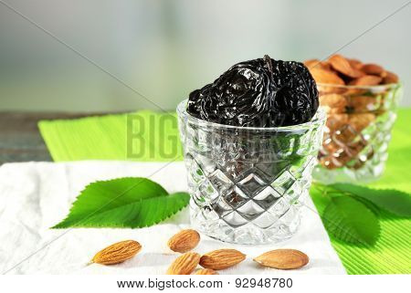Prunes and almonds in glasses with leaves on green napkin, closeup