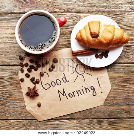 Cup of coffee with fresh croissant and Good Morning massage on wooden table, top view