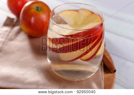 Glass of apple cider with fruits and cinnamon on table close up