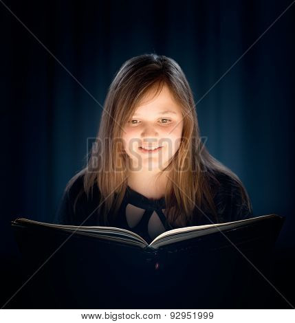Young girl with long hair reading a book in a dark room