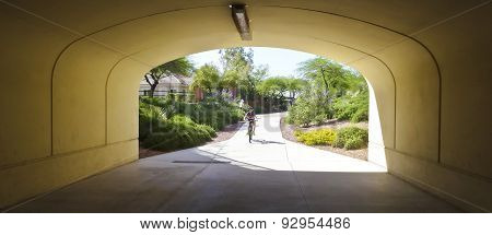 A Boy On A Bike Rides Toward A Tunnel