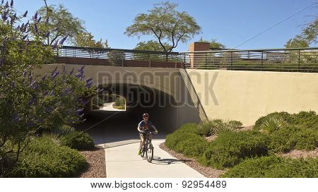 A Boy On A Bike Emerges From A Tunnel