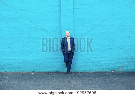 Thinking businessman and turquoise wall
