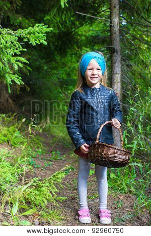 Little girl gathering mushrooms in autumn forest