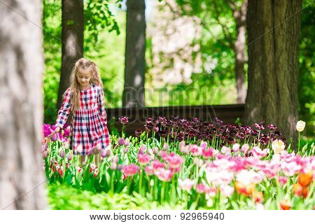 Little adorable girl at summer colorful tulips garden