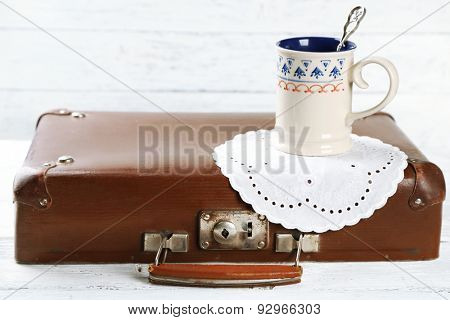 Old wooden suitcase cap cup with  tea on it, on wooden background