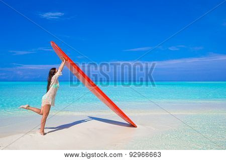 Happy beautiful surfer woman at white beach with her surfboard