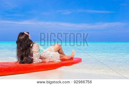 Happy beautiful surfer woman at white beach on red surfboard