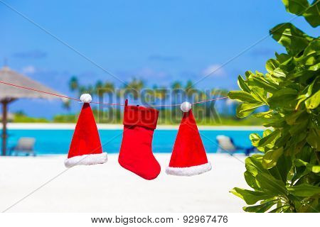 Red Santa hats and Christmas stocking hanging on tropical beach