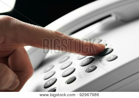 Finger pressing number button on telephone to make a call, close up