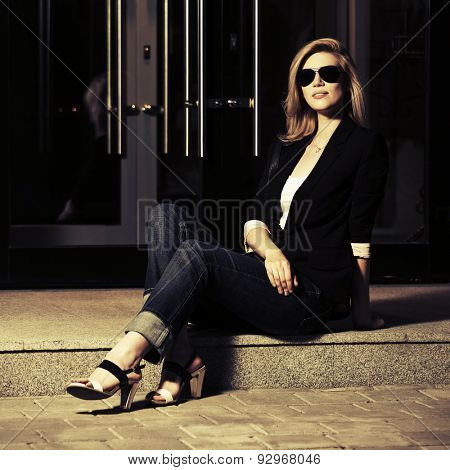 Young fashion woman in sunglasses sitting at the mall doorway