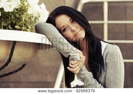 Happy young fashion woman with a flower daydreaming