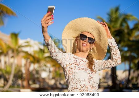 Woman taking selfie photo on vacation in tropical resort