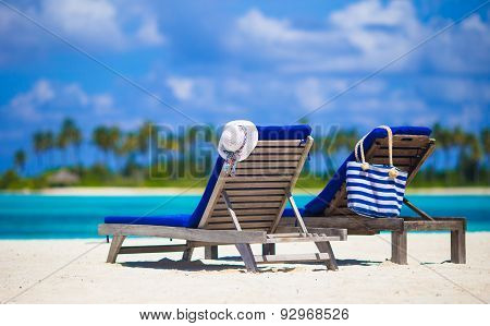 White hat and bag on lounge chairs at tropical sandy beach