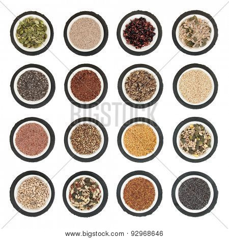 Large seed super food selection in  porcelain bowls over slate rounds and white isolated background.