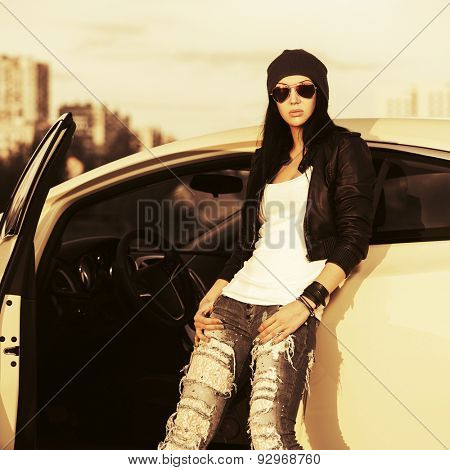 Young stylish fashion woman in sunglasses by her car outdoor