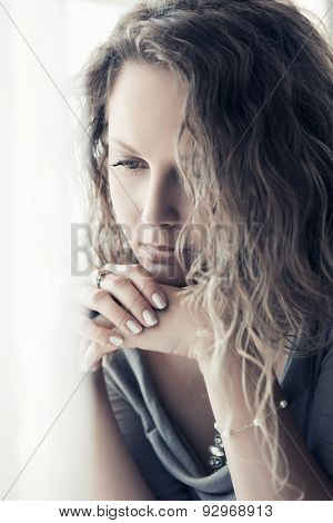 Sad beautiful woman with long curly hairs in depression looking down