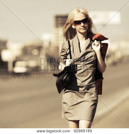 Young fashion blonde woman with handbag walking on a city street