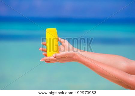 Closeup suncream bottle background blue sea