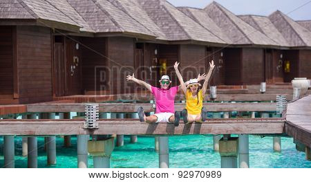 Young family of two on beach jetty at tropical island