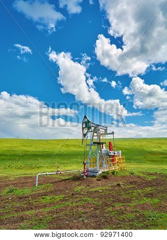 Pumping Unit For Pumping Oil On A Green Meadow Against A Blue Sky With Clouds In Summer