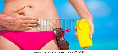 Closeup female hand applying with sunscreen on white beach