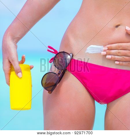 Young woman applying with sunscreen on white beach